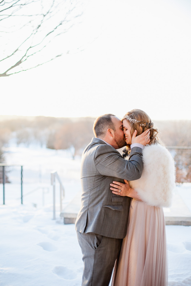 Bride and groom kissing during winter wedding.