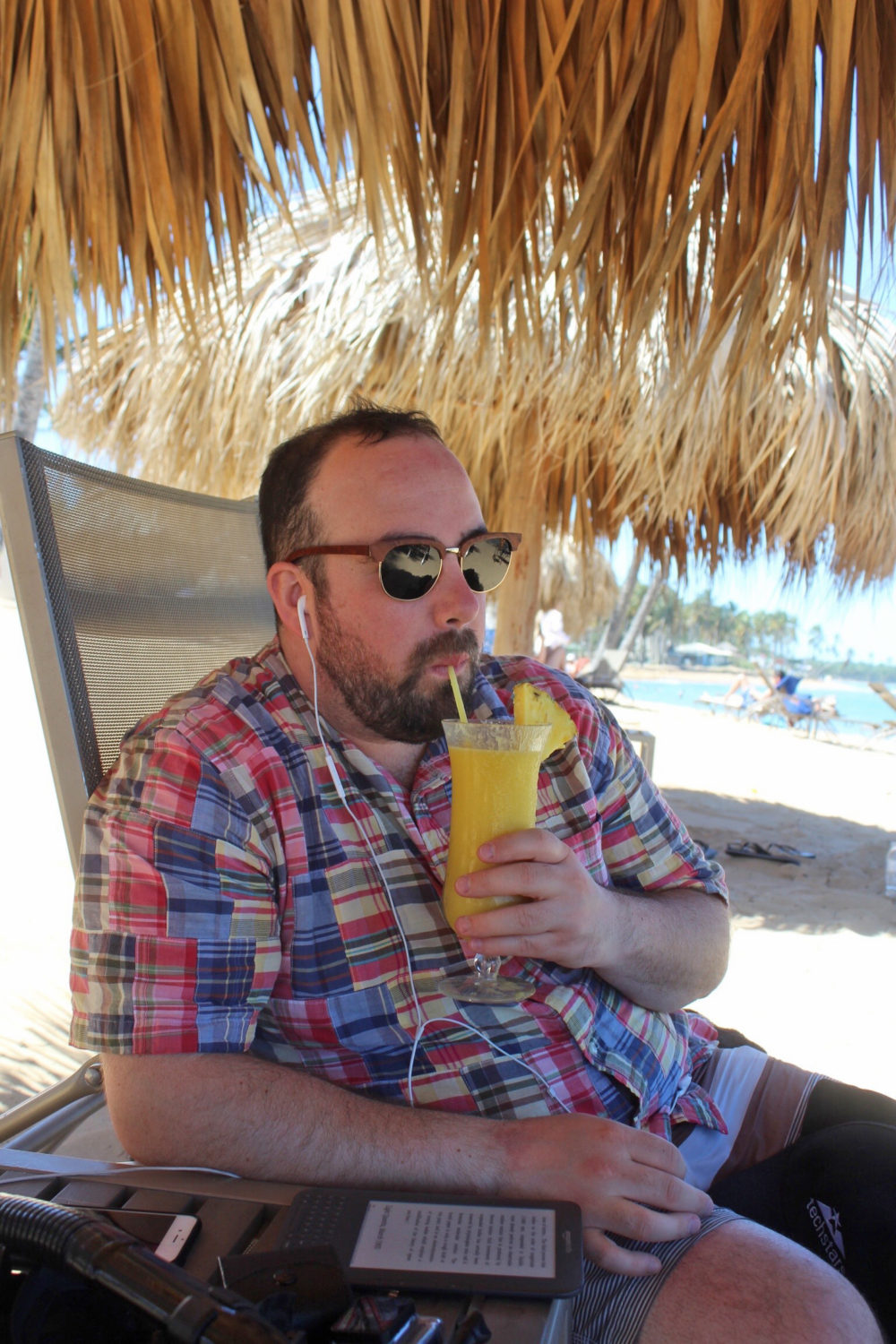 men's beach style, relaxing and sipping on a pina colada